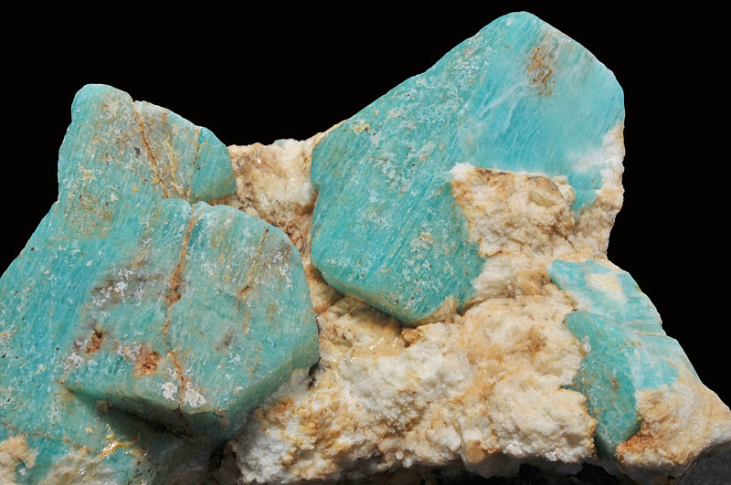 Close up image of the texture of a blue-green amazonite stone and a black background
