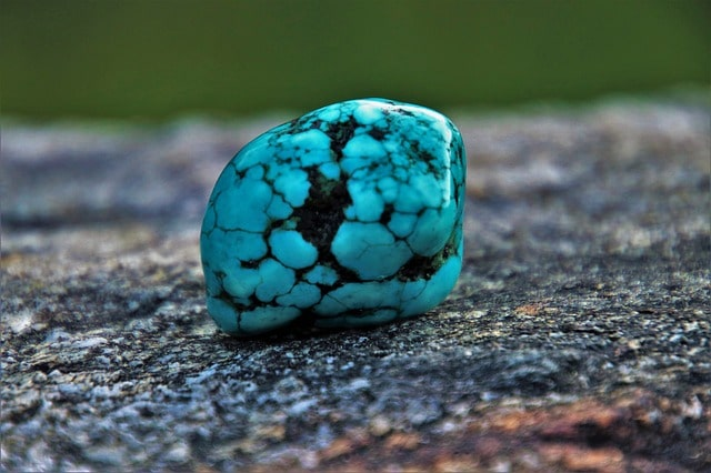 Close up image of a small, smooth turquoise stone with light blue and black lines