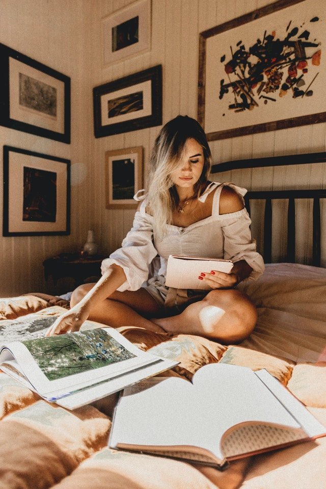 Woman on bed reading books and wearing a cute and comfortable outfit